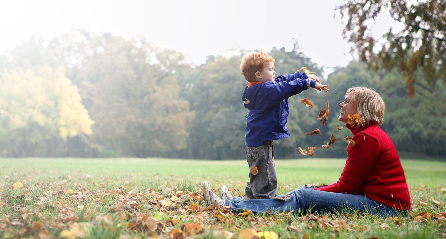 child playing in leaves with mother